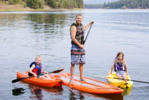 Attractive young family kayaking and paddle boarding together on a beautiful lake. Smiling and enjoying the outdoors together as a happy family